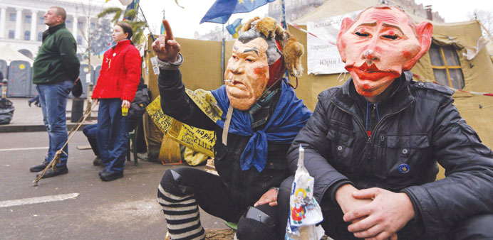 Protesters wearing masks depicting Ukrainian President Viktor Yanukovych and Russian President Vladimir Putin attend a rally at Independence Square.